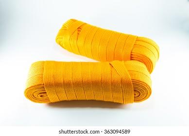 Orange rope rolls flat on white background.