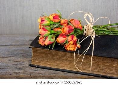 orange rose bouquet with raffia bow on vintage Bible