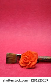 An orange rose with a paintbrush isolated on a pink background
