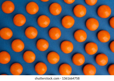 Orange round chocolate candies on a blue background with shadow