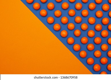 Orange round chocolate candies on a blue background with space for text. Top view.