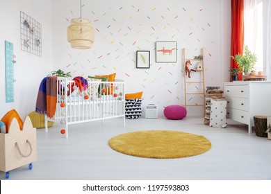 Orange round rug and posters in colorful kid's room interior with cradle and wooden crate. Real photo
