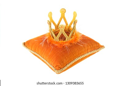 Orange royal velvet pillow with crown isolated over white background