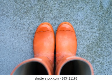 orange rubber boots on a concrete surface with copy space, top view, horizontal