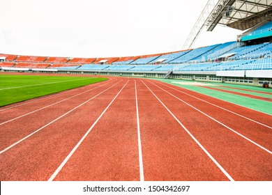 The orange running track has grass around it.