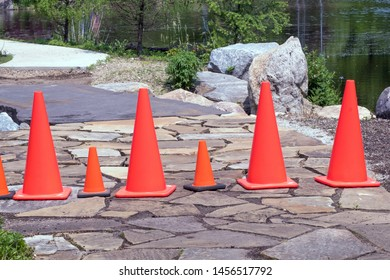 Orange safety cones, both large and small, block off a flagstone road in a pretty garden