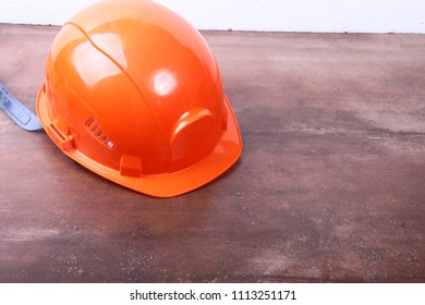 Orange safety engineer helmet on brown background