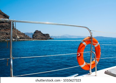Orange safety flotation device on the side of a boat with the ocean in the background