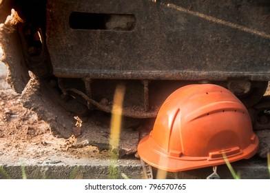 Orange safety helmet near wheel of excavator at construction site.