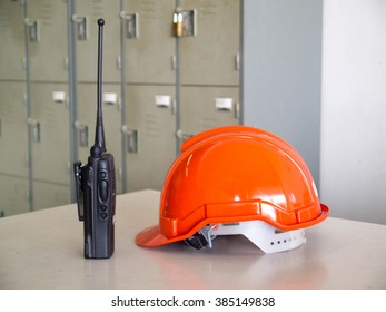 Orange safety helmet with walky-talky on table