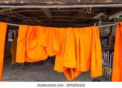 Orange and saffron robes of Buddhist monks hanging on wooden.Thailand