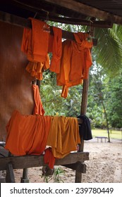 Orange and saffron robes of Buddhist monks hanging on wooden temple porch