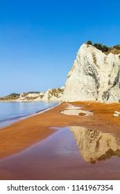 Orange sands beach with high white rocks