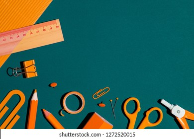 Orange school accessories on a blue background. Creative flat design with copy space.