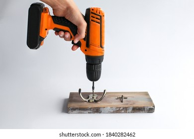 An orange screwdriver in a man's hand is screwing a hook to the board.