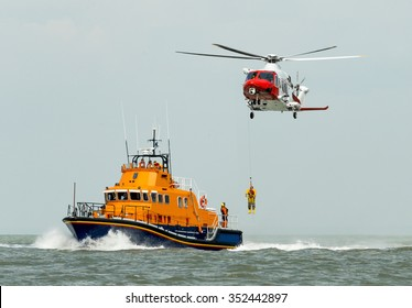 orange sea rescue boat at sea off south coast of Britain man being winched to emergency rescue helicopter