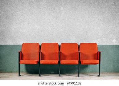 Orange seats from the old gray walls. A number of four seats. Chairs against the wall.