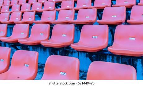 orange seats on the grandstand of the football stadium.