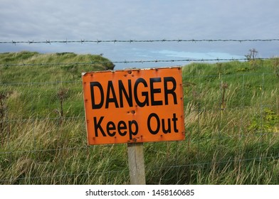 Orange sign DANGER Keep Out in front of barbed wire against the background of a cliff with green grass