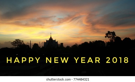 The orange sky above the temple roof and trees. 2018 HAPPY NEW YEAR letters are on the image with the black part of the view