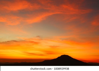 Orange sky over silhouette mountain in the morning. twilight sky with silhouette mountain at horizon. Sunrise behind the silhouette mountain with a partly cloudy sky