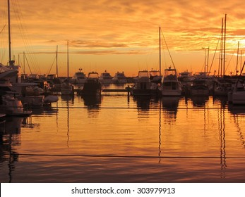 Orange sky of a Summer Sunset Over Hillarys Harbour, Perth, Western Australia reflected in the still tranquil harbour waters.