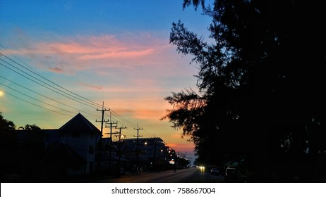 Orange sky tone with dark shadow of tree and town