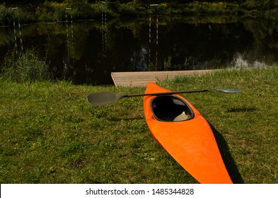 orange slalom boat with an oar stands on the bank of the river with a gate for slalom
