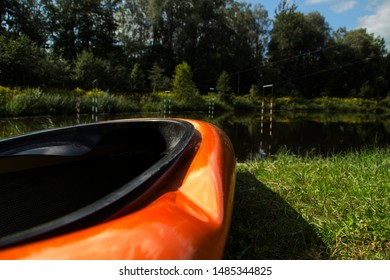 orange slalom boat stands on the bank of the river with a gate for slalom