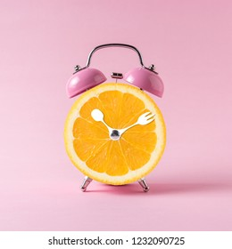 Orange slice alarm clock on pink background. Minimal business concept.