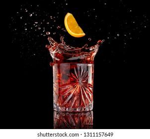 orange slice falling into a splashing negroni isolated on black