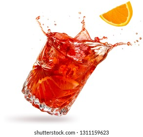 orange slice falling into a splashing negroni tilted on white background