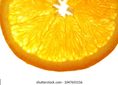 Orange slice on a white background. Thin slice of orange on a white light table orange appears to be glowing, bright. Eating healthy, citrus fruits are full of vitamin C.