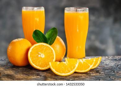orange sliced and orange juice glasses with green leaf on wooden table