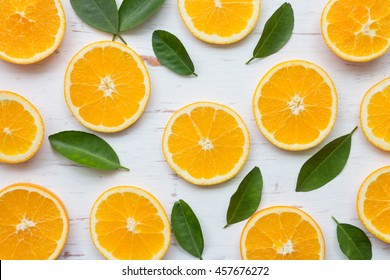 Orange slices on white rustic wooden background, top view, flat lay, summer and healthy concept