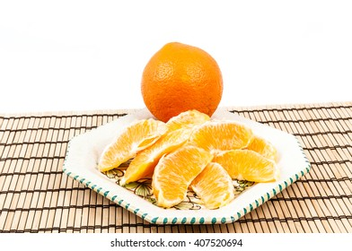 Orange slices in the plate on wooden mat