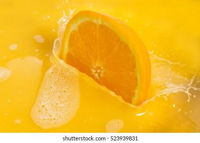 Orange Slices Splashing into Orange Juice on White Background