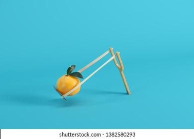 Orange in a slingshot on blue background. Minimal fruit idea concept.