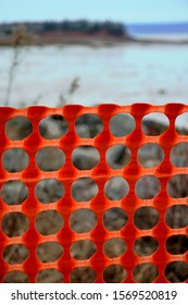 Orange snow fence with round holes in front of grass background, with ocean and forest in distance