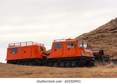 Orange snowcat with second wagon. Another vehicle with snowplow seen in the background.