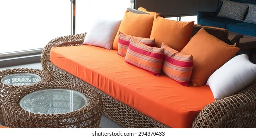 orange sofa with the colorful pillows