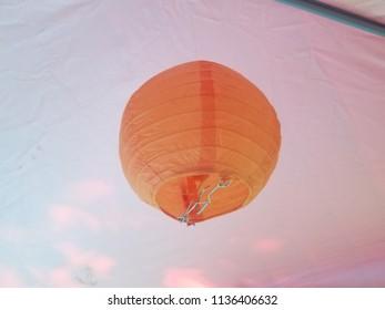 orange spherical paper lantern hanging from tent