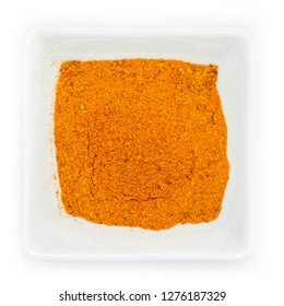 Orange spicy madras curry powder in a white bowl in top view