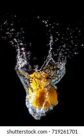 orange splashing in the water black background