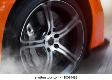 Orange Sport Car with detail on drifting and smoking wheels/tires doing burnouts