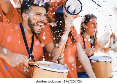 Orange sport fans screaming while supporting their team out of the stadium - Football supporters having fun at competion event - Focus on man face