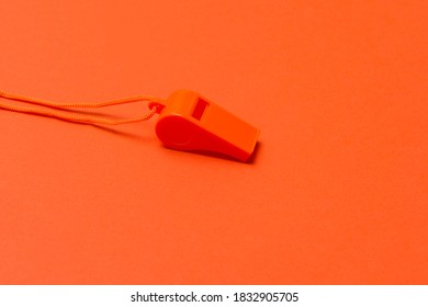 Orange sports whistle on orange background. Concept- sport competition, referee, statistics, challenge. Basketball, handball, futsal, volleyball, soccer, baseball, football and hockey referee whistle