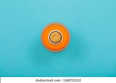 orange spray can on cyan background