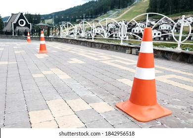 Orange striped road cones on a pavement. Safety equipment for traffic on a street, car barricade equipment for driving lessons. Plastic security cone for caution, sign to be careful behind the wheel.