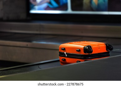 Orange suitcase waiting to be picked up